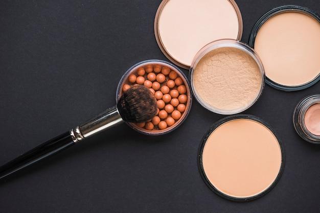 Verhoogde weergave van gezichtspoeder; bronzing parels en make-up borstel op zwarte achtergrond