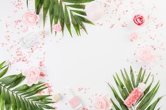 Verhoogde weergave van himalayazout; verlaat; nagellak; fles; vochtinbrengende crème en bloemen op witte achtergrond