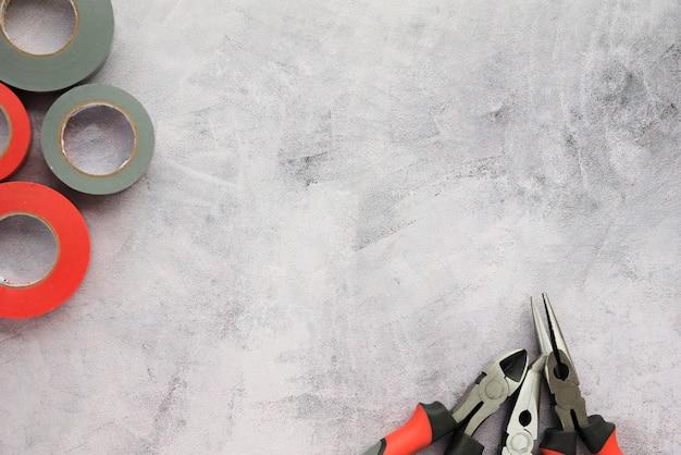 Verhoogde weergave van isolatietape en tang op betonoppervlak