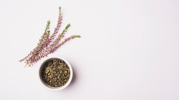 Verhoogde weergave van lavendel bloemen in de buurt van droge bloemblaadjes in kom op wit oppervlak