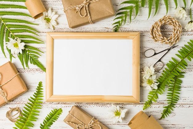 Verhoogde weergave van leeg frame omgeven door geschenken; bladeren en witte bloemen