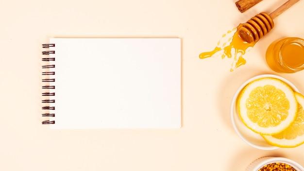 Verhoogde weergave van lege kladblok met schijfje citroen en honing