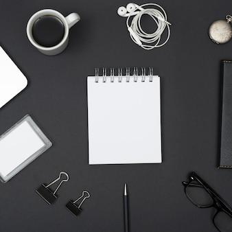 Verhoogde weergave van oortelefoon; koffiekop; paperclips; lenzenvloeistof; met lege witte kladblok gerangschikt op zwarte achtergrond