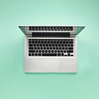 Verhoogde weergave van opengeklapte laptop op groene achtergrond