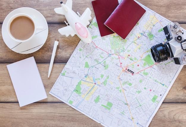 Verhoogde weergave van paspoort; kaart; vliegtuig; camera; papier en thee beker op houten achtergrond
