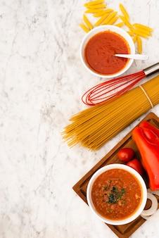 Verhoogde weergave van rauwe pasta en tomatensaus op marmeren gestructureerde achtergrond
