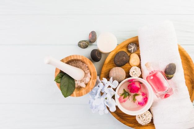Verhoogde weergave van spa-stenen; zout; handdoek; bloemen en olie op witte achtergrond