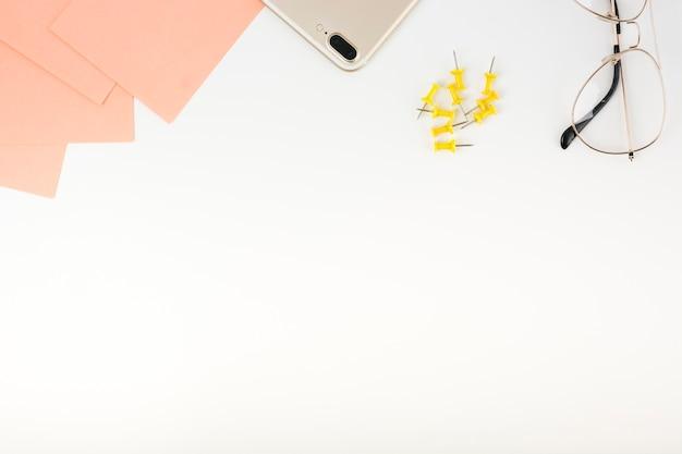 Verhoogde weergave van zelfklevende biljetten; smartphone; duw spelden en bril bij de bovenkant van witte achtergrond