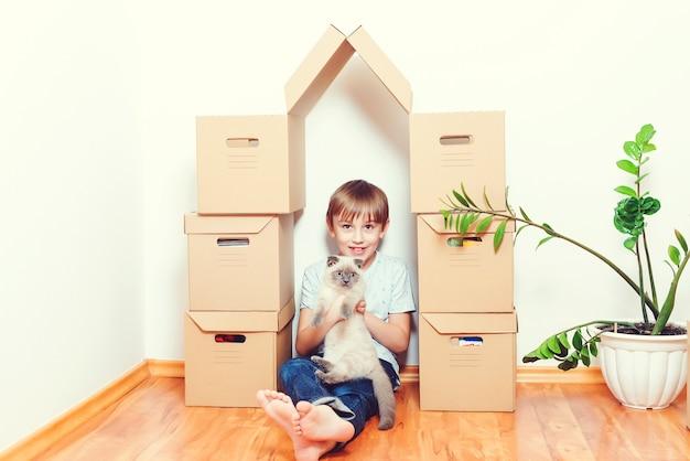 Verhuisdag. gelukkig kind en kat die samen plezier hebben op de verhuisdag in een nieuw huis.
