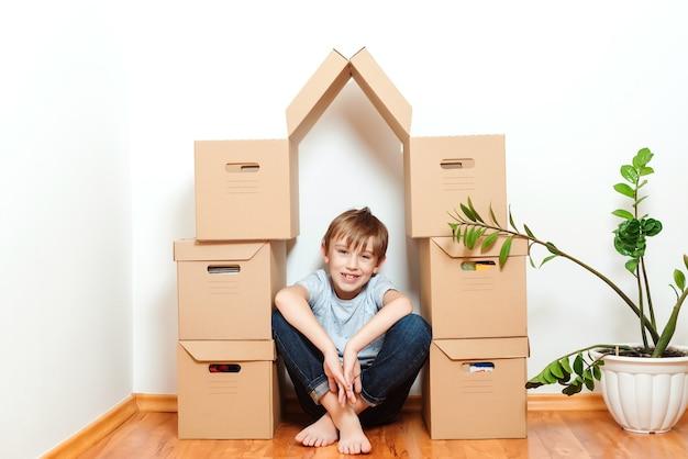 Verhuisdag. gelukkige jongen die plezier heeft in de verhuisdag. huisvesting van een jong gezin met kind.