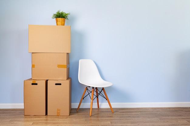 Verhuisdozen met ingepakte spullen en stoel om te verplaatsen