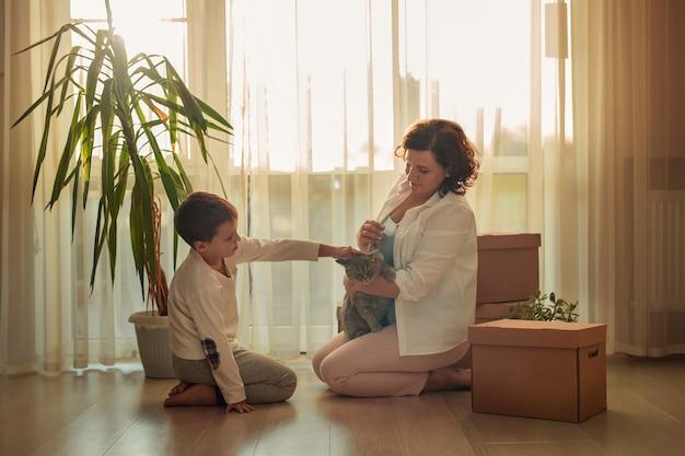 Verhuizen naar een nieuw huisgezin moeder en zoon met kartonnen dozen en kat