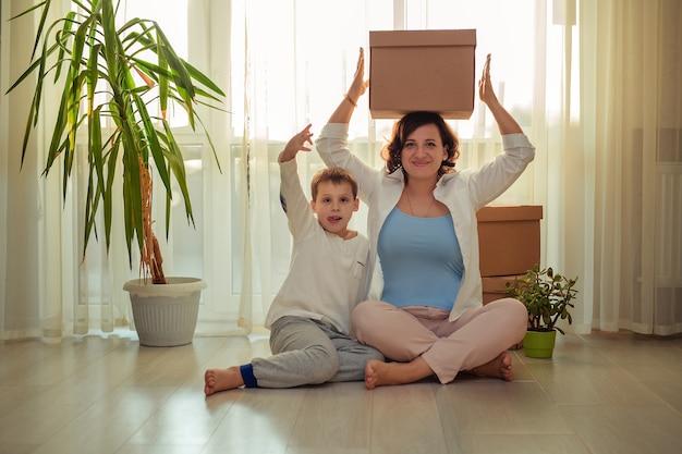 Verhuizen naar een nieuw huisgezin, moeder en zoon met kartonnen dozen