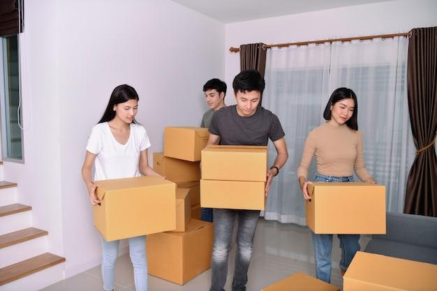 Verhuizingen concept. young houdt hun spullen in een kartonnen doos. jong blij in het nieuwe huis.