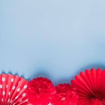 Verity van rode valse origamibloemen over blauwe oppervlakte