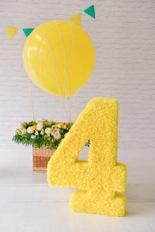 Verjaardag 4 jaar oud viert verjaardag in een versierde gestileerde studio, nummer 4 en grote ballon. gele stijl.