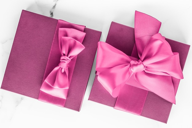 Verjaardag bruiloft en girly branding concept roze geschenkdoos met zijden strik op marmeren achtergrond meisje b...