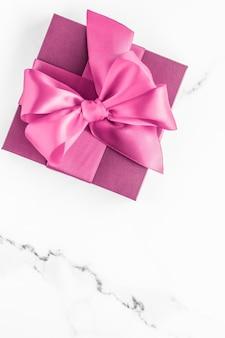 Verjaardag bruiloft en girly branding concept roze geschenkdoos met zijden strik op marmeren achtergrond meisje baby shower aanwezig en glamour mode cadeau voor luxe schoonheid merk vakantie flatlay art design