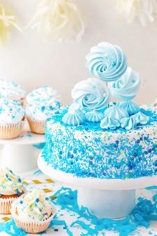 Verjaardag candy bar met blauwe cake, cupcakes en meringue.