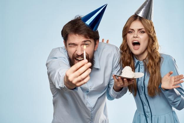 Verjaardag corporate jonge man en vrouw met cake op geïsoleerde achtergrond discopartij