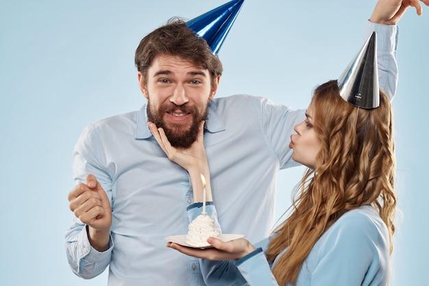 Verjaardag corporate jonge man en vrouw met cake op geïsoleerde muur discopartij.