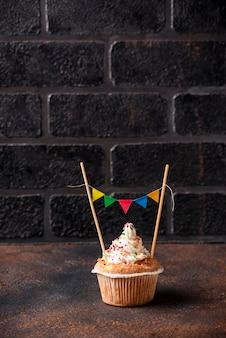 Verjaardag cupcake met room en kleurrijke slinger