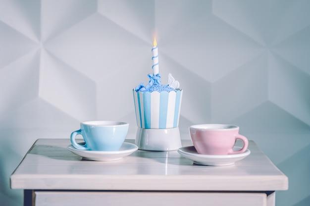 Verjaardag cupcake met verjaardagskaars en kopje thee.