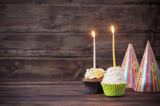 Verjaardag cupcakes met kaarsen op oude donkere houten tafel