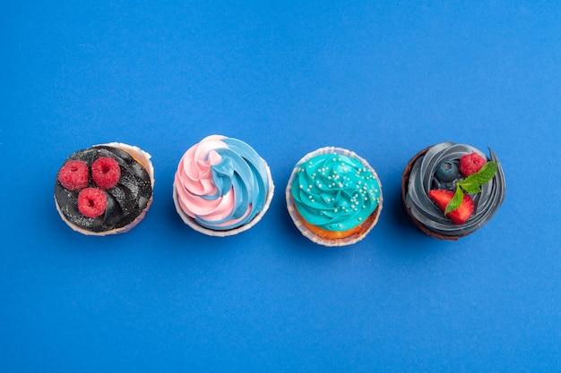 Verjaardag cupcakes op blauwe dichte omhooggaand als achtergrond