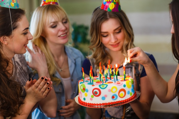 Verjaardag, de vrouw steekt kaarsen op de taart aan.