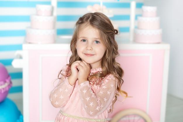 Verjaardag en geluk concept - gelukkig meisje met snoep op candy bar. portret van een mooi klein meisje. weinig leuk meisje die met suikergoed in het huis spelen. kleine dame. vakantie