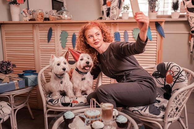 Verjaardag honden. stralende roodharige vrouw die dol is op haar huisdieren en foto's maakt met haar verjaardagshonden