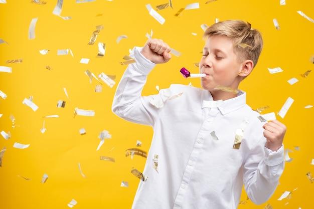 Verjaardag jongen portret. feestelijke vreugde. gelukkig kind dansen met partij hoorn in confetti regen geïsoleerd op geel.