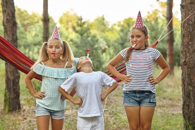Verjaardag, kindertijd en feestconcept - close-up van gelukkige kinderen die op feesthoorns blazen en plezier hebben in de zomer buiten