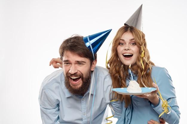 Verjaardag man en vrouw met een cupcake en een kaars in een feestmuts, witte muur