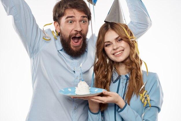 Verjaardag man en vrouw met een cupcake en een kaars in een feestmuts, witte ruimte