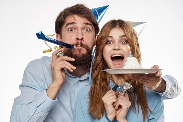 Verjaardag man en vrouw met een cupcake en een kaars in een feestmuts