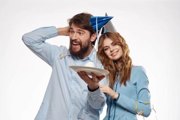 Verjaardag man en vrouw met een cupcake en een kaars in een feestmuts,