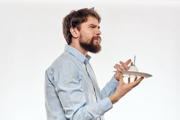 Verjaardag man met een cupcake en een kaars in een feestmuts