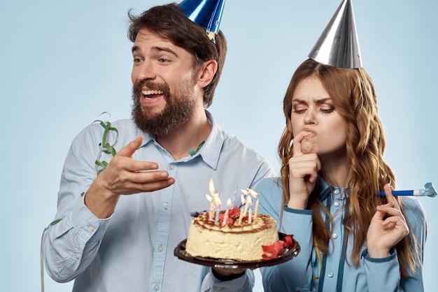 Verjaardag man vrouw in feestmutsen op een blauw en een taart met kaarsen