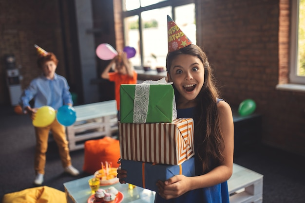 Verjaardag. mooi meisje in een hoed die presenteert en opgewonden kijkt
