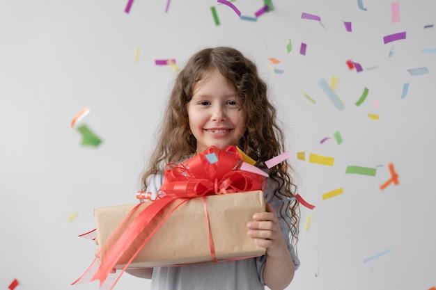 Verjaardag. mooi meisje in een witte jurk met haar staat voor het raam.