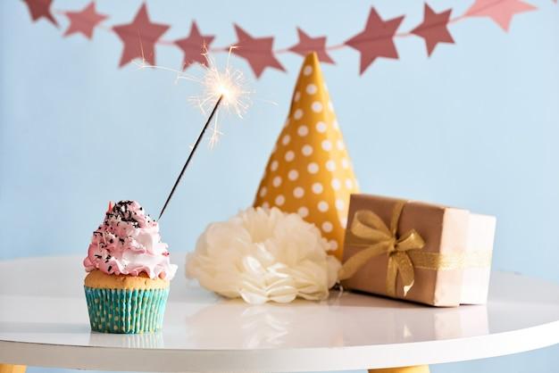 Verjaardag partij achtergrond met cupcake, feestmuts en heden