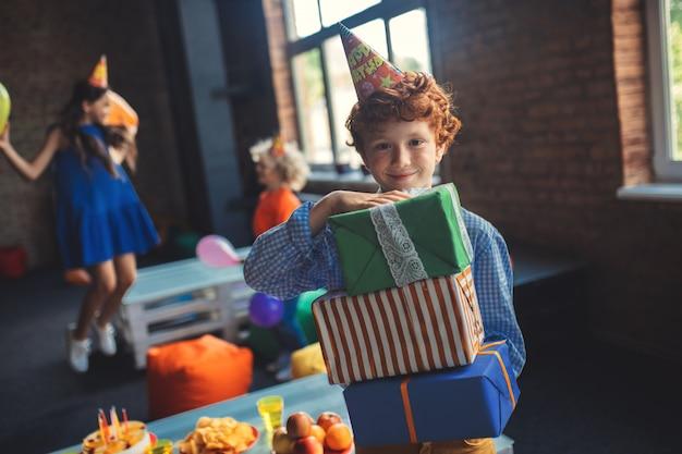 Verjaardag. schattige roodharige jongen bedrijf presenteert en glimlachen
