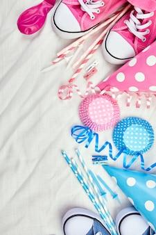 Verjaardag tweeling jongen en meisje plat lag, bovenaanzicht en kopieer ruimte voor tekst, frame of achtergrond met roze en blauwe festivalartikelen, feestmutsen en slingers, feest wenskaart.