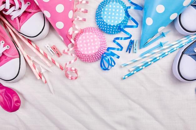 Verjaardag tweeling jongen en meisje plat lag, bovenaanzicht en kopieer ruimte voor tekst, frame of achtergrond met roze en blauwe festivalartikelen, feestmutsen en slingers, feest wenskaart