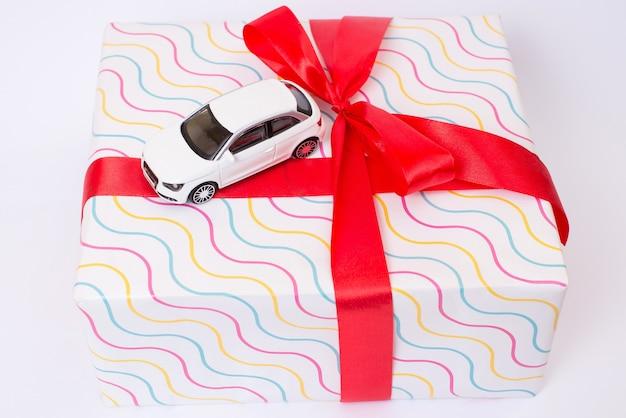 Verjaardag vakantie evenement loterij concept. boven boven bovenaanzicht close-up foto van mooie kleine speelgoed witte auto geplaatst op grote verpakte geschenkdoos met heldere strik geïsoleerd op een grijze achtergrond