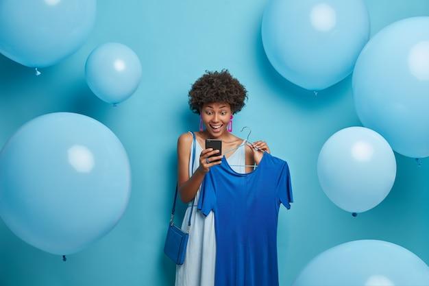 Verjaardag, vakantie, kledingconcept. blije onder de indruk vrouw staart met verbaasde blije blik naar smartphonescherm, krijgt onverwacht bericht, kiest jurk aan hangers, jurken in alles blauw