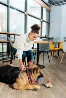 Verjaardag van de hond. krullend stralende aantrekkelijke vrouw liefdevolle haar hond viert zijn verjaardag in een mooie bakkerij