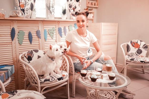 Verjaardag van honden. donkerharige vrouw met wit t-shirt die de verjaardag van twee honden viert